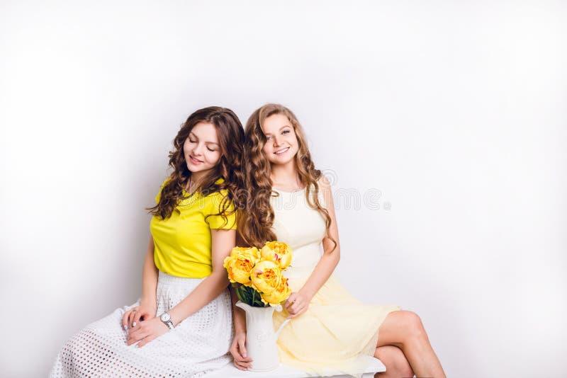 Foto do estúdio de duas meninas de sorriso que sentam-se ombro a ombro A morena vestem a saia branca e o t-shirt amarelo, e louro imagens de stock royalty free