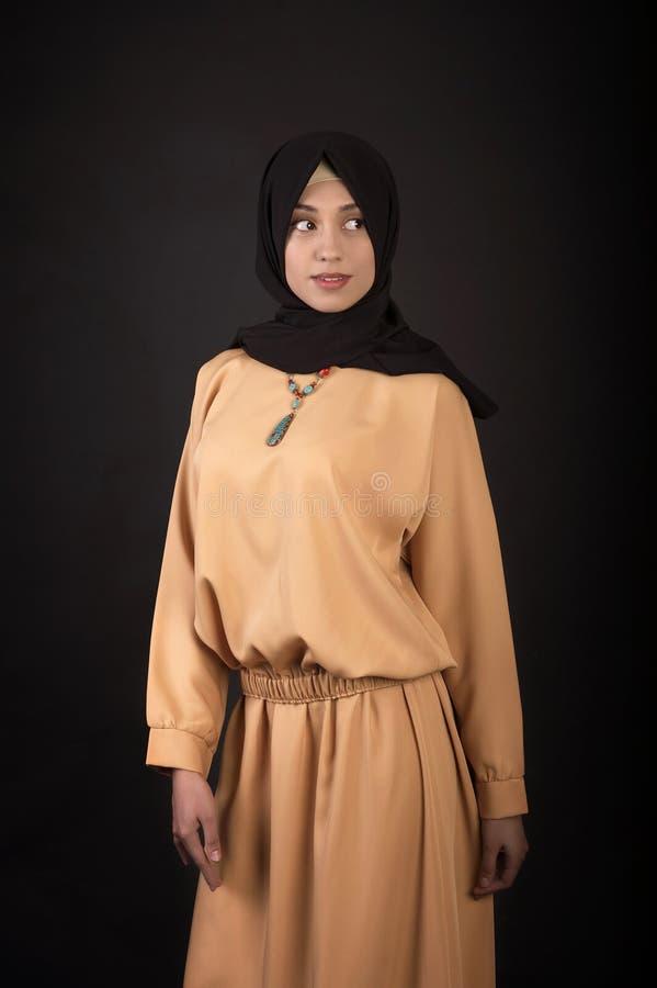 Foto do estúdio de um tipo oriental da jovem mulher bonita completo, em um fundo escuro, vestido no estilo muçulmano imagens de stock royalty free