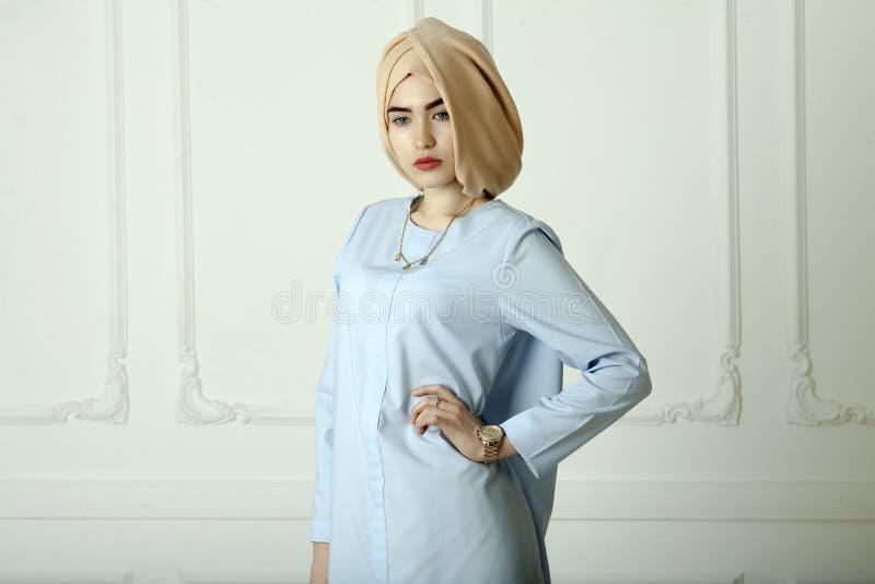 A foto do estúdio de uma jovem mulher oriental datilografa dentro a roupa muçulmana moderna, a mantilha bonita e um relógio de ou foto de stock royalty free