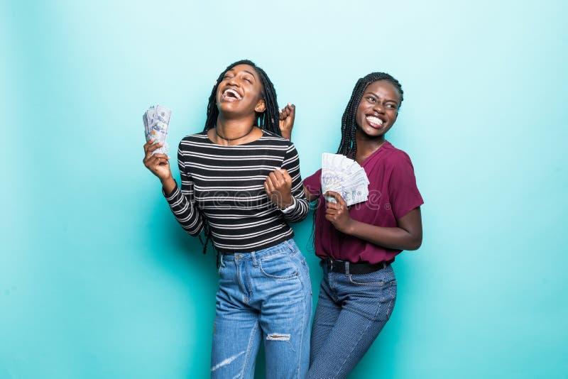 Foto do grito da vitória das mulheres novas do afro-americano com as cédulas do dólar isoladas sobre o fundo azul fotografia de stock royalty free
