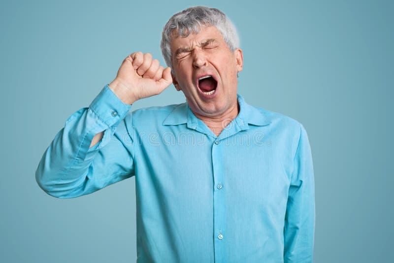 A foto do homem aposentado de cabelo cinzento cansado sente sonolento, boceja como sente cansado, abre a boca extensamente, vesti foto de stock royalty free