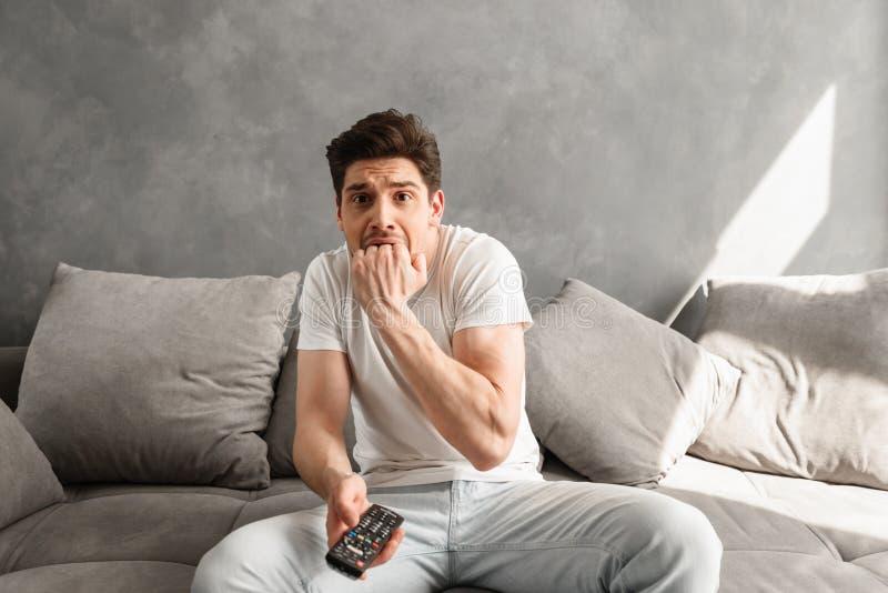 Foto do homem assustado que morde seu punho no medo ao sentar-se no cou fotos de stock royalty free