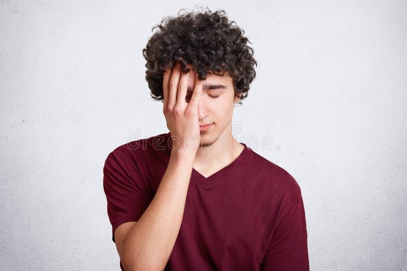A foto do homem considerável sobrecarregado cansado com cabelo escuro encaracolado, cara das tampas com mão, olhares frustrados,  foto de stock royalty free
