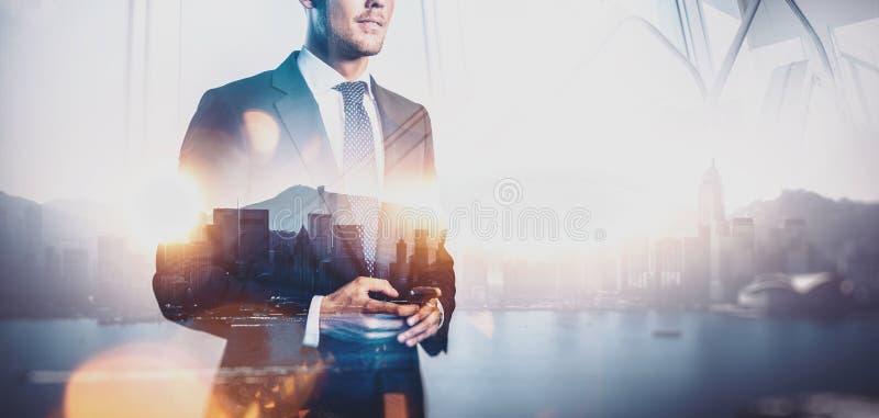 Foto do homem de negócios que guarda o smartphone Exposição dobro, cidade no fundo largamente imagem de stock royalty free