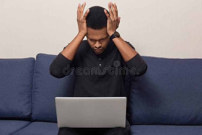 A foto do homem descascado escuro sobrecarregado fatigante tem a enxaqueca terrível, vestida ocasionalmente, trabalhos no laptop, imagens de stock