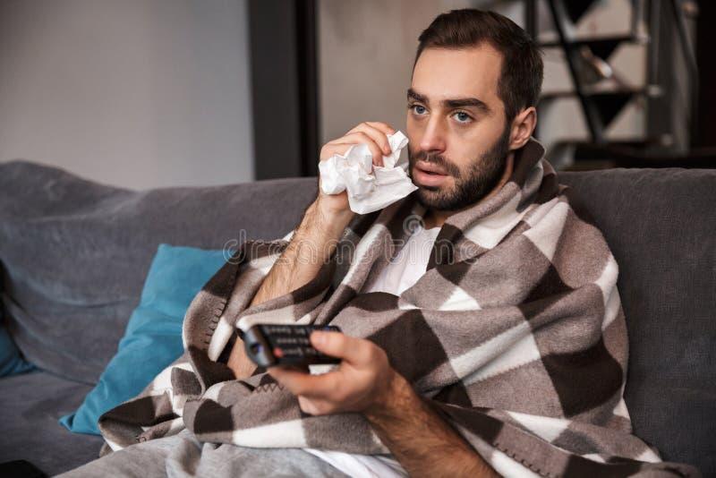 Foto do homem descontentado 30s que é doente ao sentar-se envolvida na cobertura no sofá em casa imagens de stock royalty free