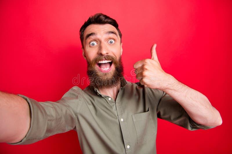 Foto do homem ectático extático considerável que veste o tiro cinzento do auto da camisa ao manusear até você quando com foto de stock