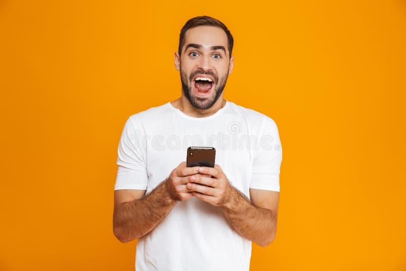 Foto do homem farpado 30s no vestuário desportivo que sorri e que guarda o smartphone, sobre o fundo amarelo fotografia de stock royalty free