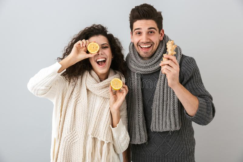 Foto do homem feliz dos pares e dos lenços vestindo da mulher que guardam limões e gengibre, isolada sobre o fundo cinzento foto de stock
