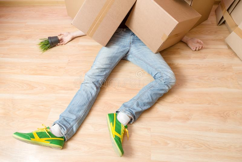 Foto do homem nas calças de brim que encontram-se sob caixas de cartão fotografia de stock