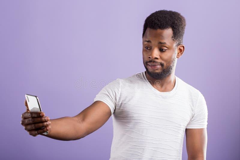 Foto do homem negro confundido surpreendido que guarda o telefone celular moderno foto de stock royalty free