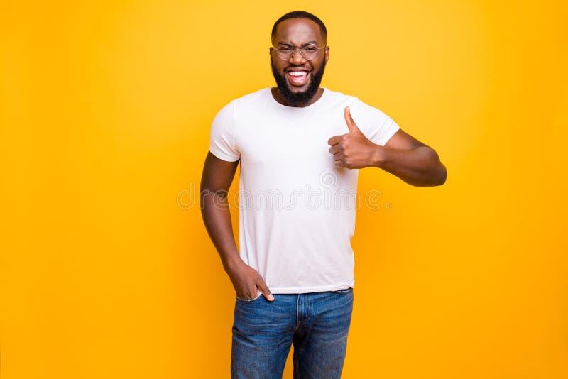 Foto do homem negro extático ocasional consistente das calças de brim vestindo da felicidade que guardam a mão na sarja de Nimes  foto de stock royalty free