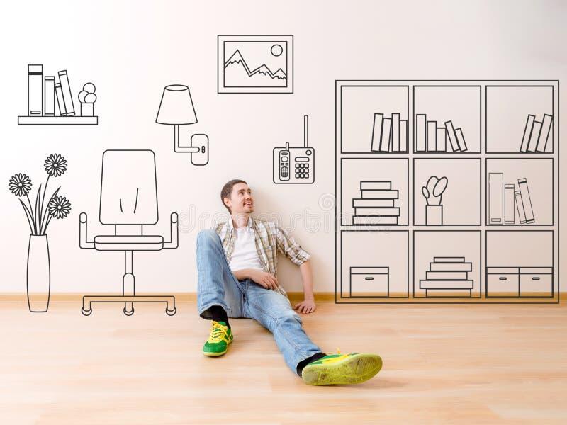 A foto do homem que senta-se no assoalho com a flor pintada da casa, pinturas na poltrona da parede, arquiva, livros foto de stock
