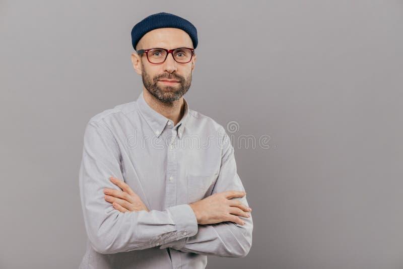 A foto do homem sério mantém a caixa dobrada os braços, vestida na camisa formal branca, chapéu elegante, levanta fazendo a fotog imagem de stock