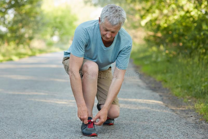 A foto do homem superior tem o exercício running exterior, sapatilhas dos laços na estrada, ruptura das tomadas após movimentar-s fotografia de stock royalty free