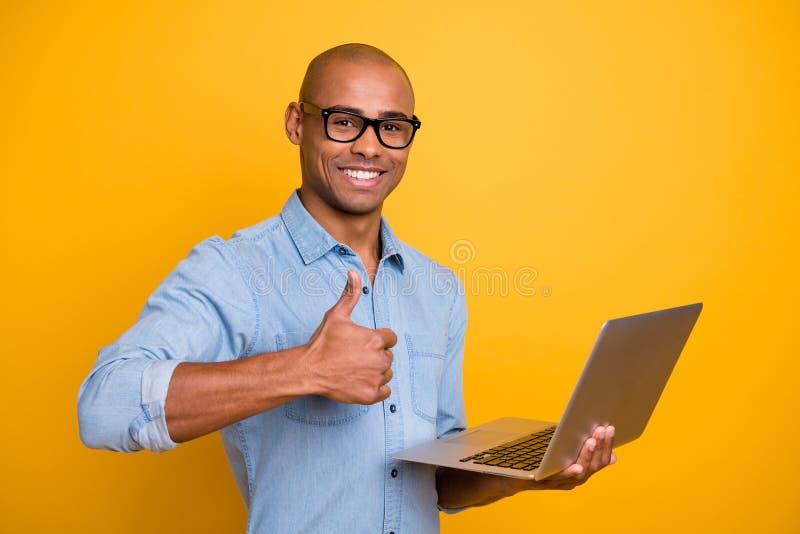 A foto do indivíduo escuro da pele que procura o polegar da posse do caderno do Web site aumentado acima da camisa da sarja de Ni imagens de stock