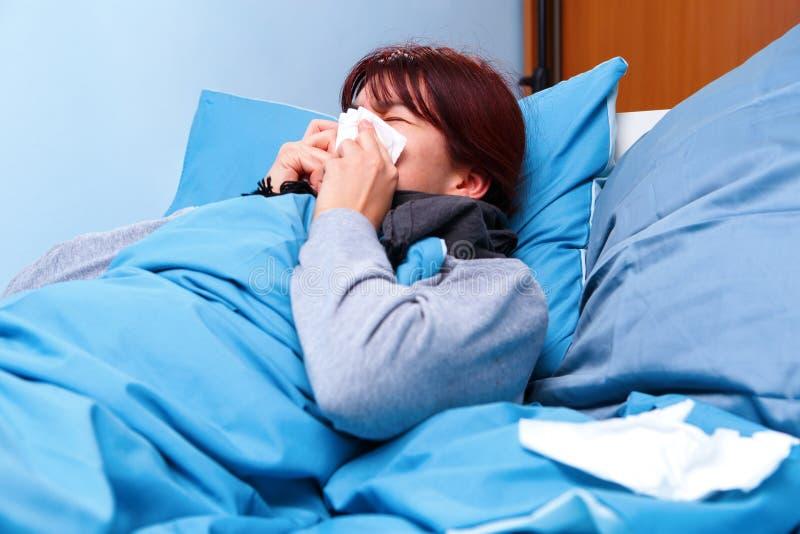 Foto do lado da menina moreno doente que funde seu nariz no lenço de papel que encontra-se na cama fotografia de stock royalty free