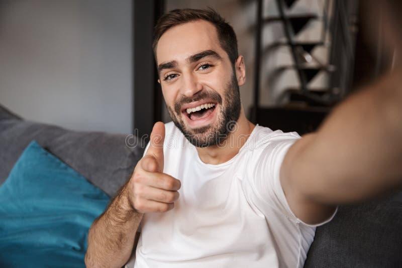 Foto do licenciado feliz que guarda e que toma o selfie no telefone celular ao sentar-se no sofá na sala de visitas fotografia de stock