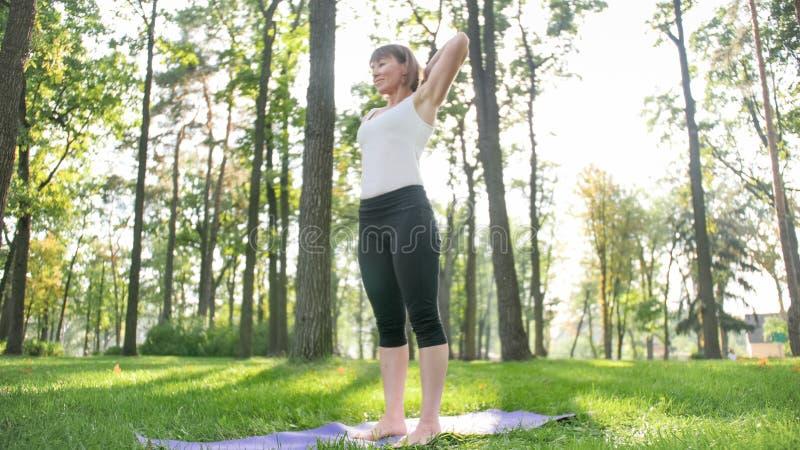 A foto do meio envelheceu a ioga praticando de sorriso da mulher e meditar no parque Mulher que estica e que faz a aptid?o na est fotos de stock