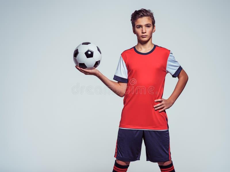 Foto do menino adolescente no sportswear que guarda a bola de futebol imagem de stock
