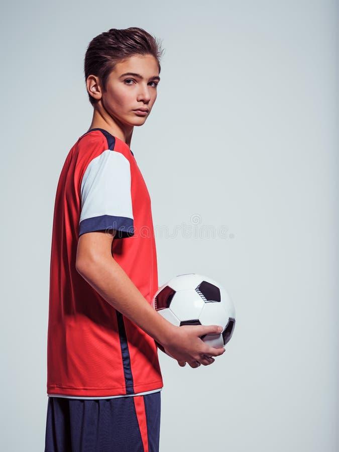 Foto do menino adolescente no sportswear que guarda a bola de futebol fotografia de stock royalty free