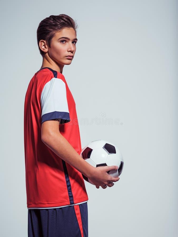 Foto do menino adolescente no sportswear que guarda a bola de futebol imagens de stock