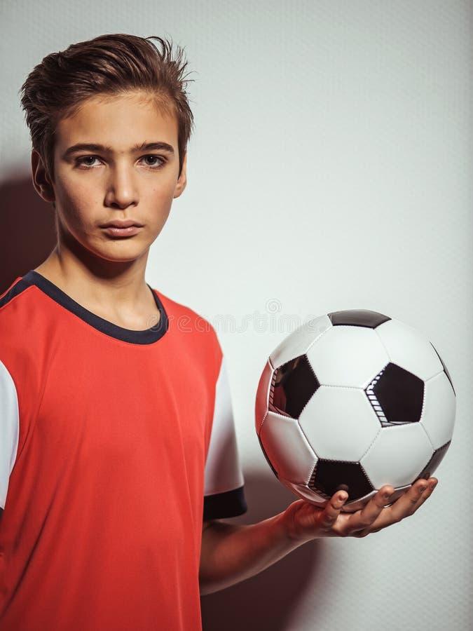 Foto do menino adolescente no sportswear que guarda a bola de futebol fotos de stock royalty free