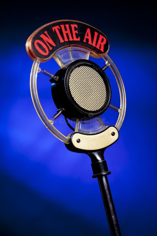 Foto do microfone de rádio no fundo azul imagem de stock