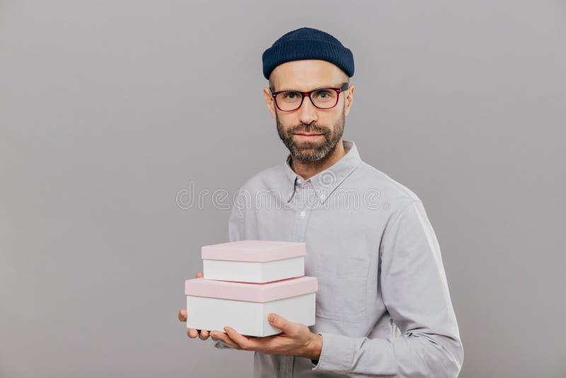A foto do modelo masculino sério vestido na roupa festiva, guarda presentes nas mãos, indo felicitar o amigo com o aniversário, p imagem de stock