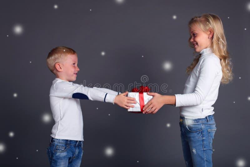 A foto do Natal do menino pequeno faz uma surpresa à menina bonita, deixou-a nevar, dá um caixa-presente imagens de stock