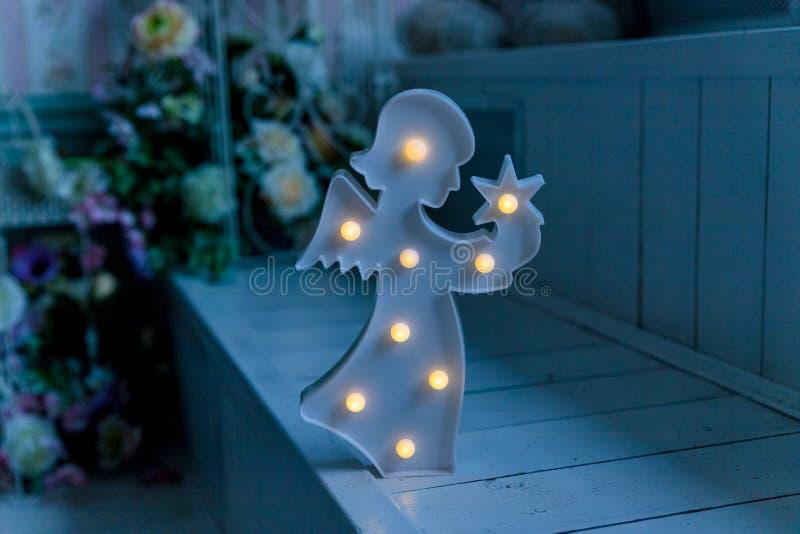 Foto do nightlight na forma do anjo na sala do ` s das crianças Lâmpada, luz da noite das crianças no quarto do ` s das crianças, imagens de stock royalty free