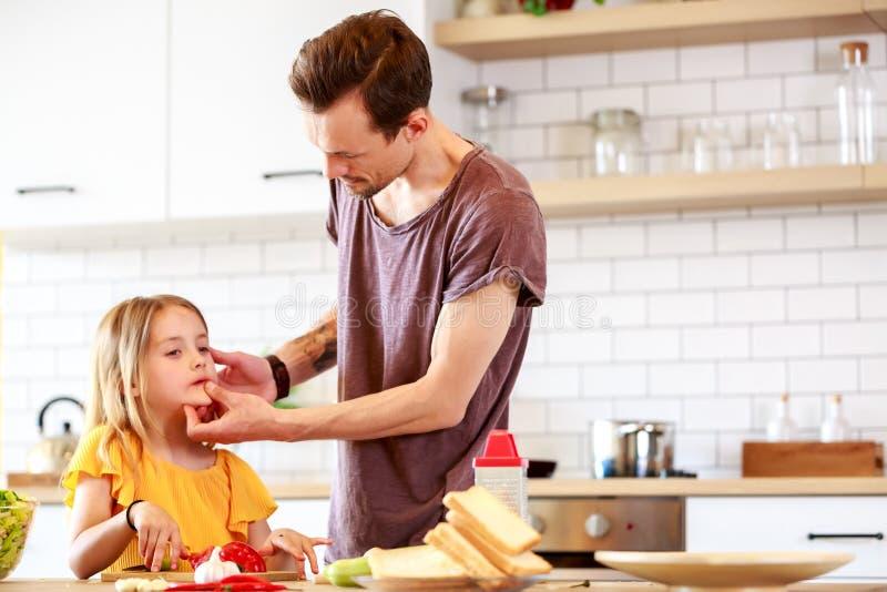 Foto do pai novo com a filha que cozinha o lunchn foto de stock