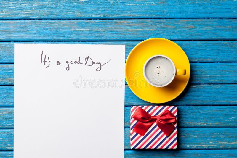 Foto do papel ele ` s um bom dia, uma xícara de café e um presente bonito em t fotos de stock royalty free