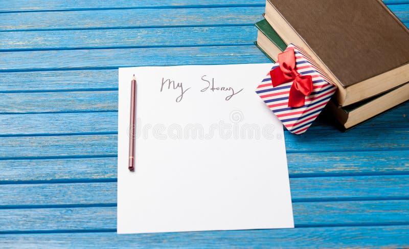 Foto do papel meus história, presente bonito e pilha dos livros no wond foto de stock