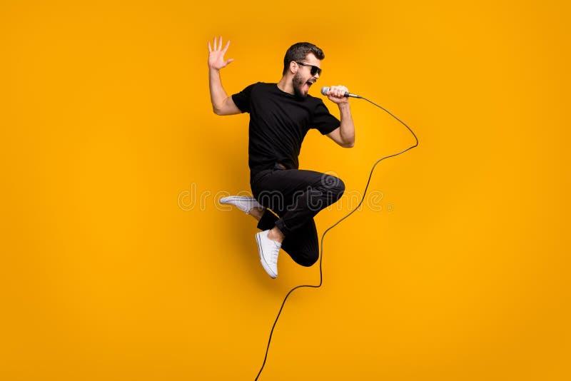 Foto do perfil do corpo inteiro de um hipster louco saltando alto segurando microfone cantando música favorita usando sol foto de stock royalty free