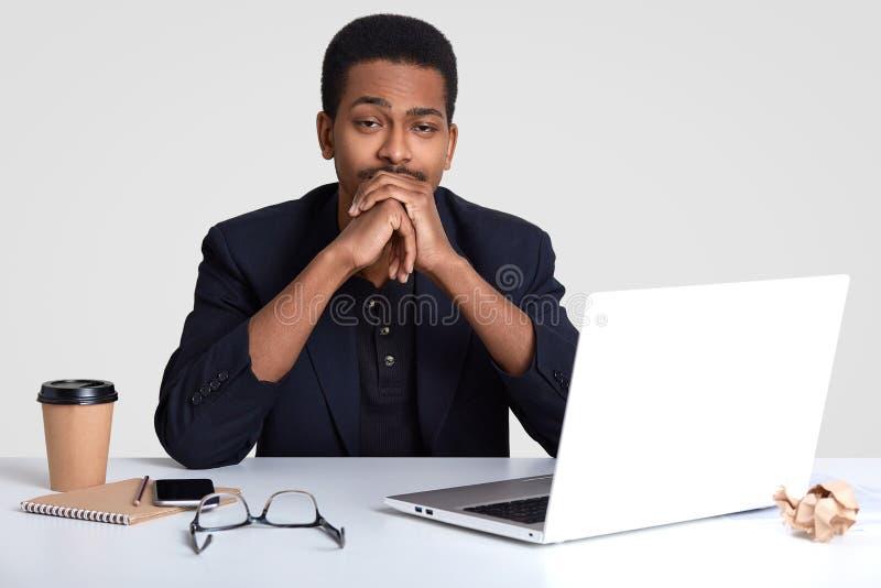 A foto do proprietário empresarial masculino próspero cansado sonolento mantém as mãos sob o queixo, precisa de desenvolver a est imagem de stock royalty free