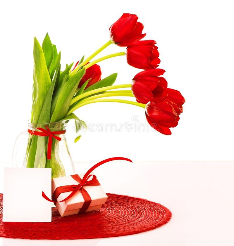 Ramalhete vermelho das tulipas com presente imagem de stock royalty free
