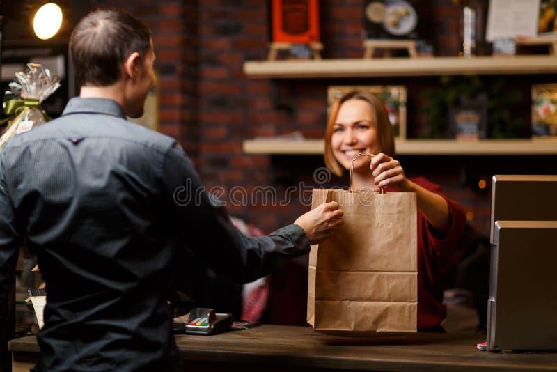 Foto do vendedor da menina com o cliente do saco de papel e do homem da parte traseira fotos de stock royalty free