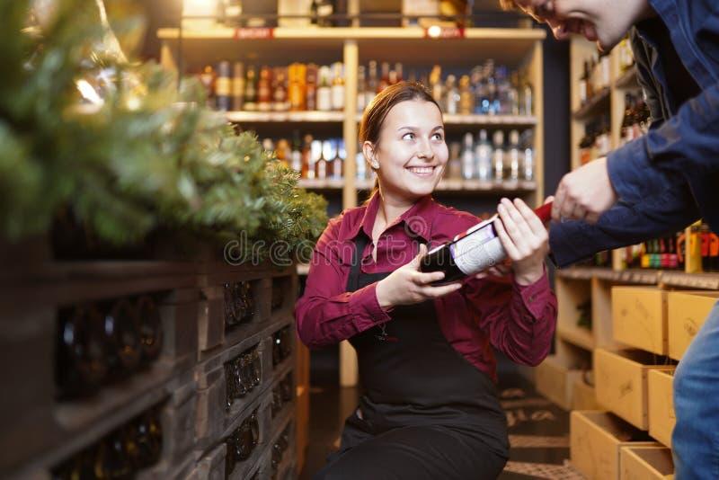 Foto do vendedor da mulher com a garrafa do vinho e do comprador imagens de stock