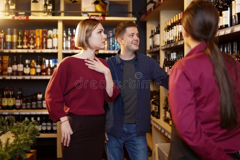 Foto do vendedor da mulher com a garrafa do vinho e do comprador fotos de stock