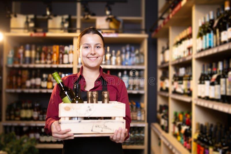 Foto do vendedor moreno novo com a caixa de madeira com vinho na loja foto de stock royalty free