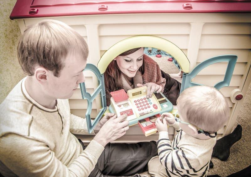 Foto do vintage da família nova que joga com caixa registadora do brinquedo dentro imagem de stock royalty free