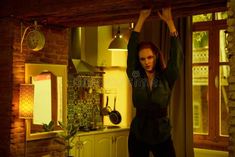 Foto do vintage da jovem mulher de cabelo vermelha bonita que levanta no apartamento velho do sótão em Tbilisi imagem de stock
