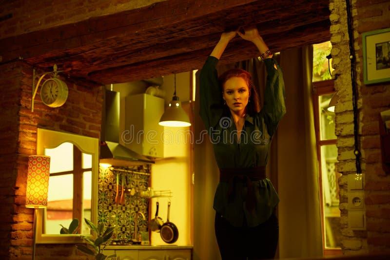 Foto do vintage da jovem mulher de cabelo vermelha bonita que levanta no apartamento velho do sótão em Tbilisi fotografia de stock