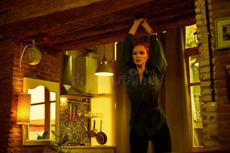 Foto do vintage da jovem mulher de cabelo vermelha bonita que levanta no apartamento velho do sótão em Tbilisi fotos de stock