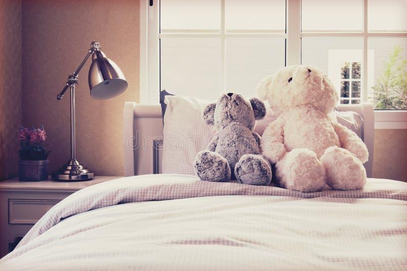 Foto do vintage da sala das crianças com bonecas e descansos na cama imagem de stock royalty free