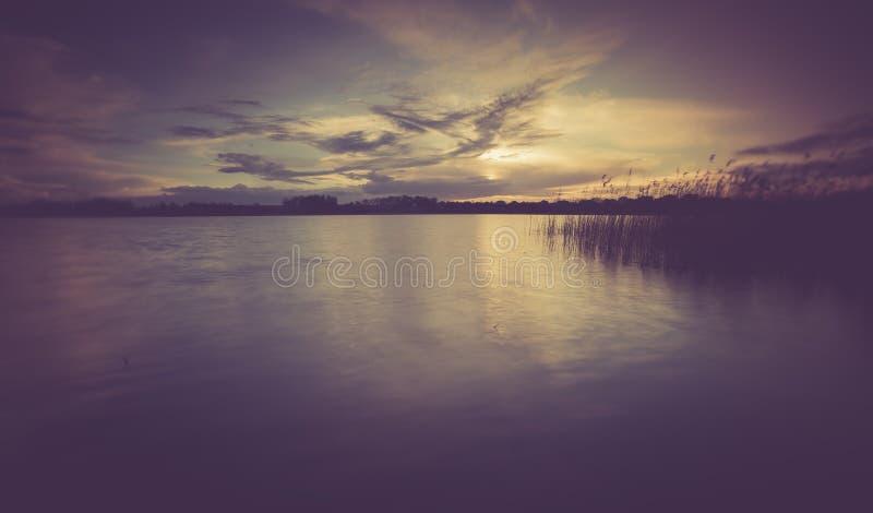 Foto do vintage do por do sol bonito sobre o lago calmo fotografia de stock royalty free