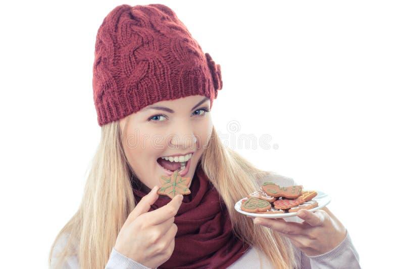 Foto do vintage, mulher de sorriso no tampão de lã e xaile que guarda pão-de-espécie, tempo do Natal foto de stock royalty free
