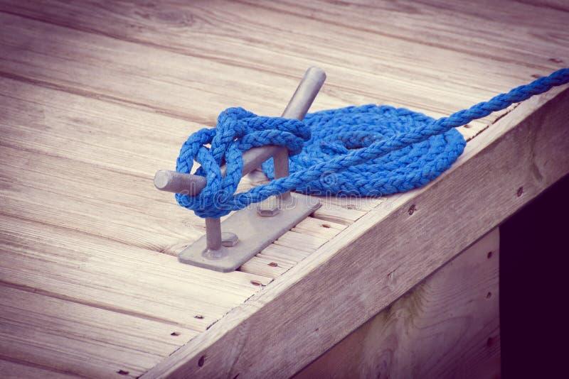 Foto do vintage, vela, corda azul e poste de amarração da amarração fotografia de stock