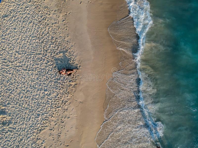 Foto do zangão da mulher que encontra-se na praia durante o por do sol fotografia de stock royalty free